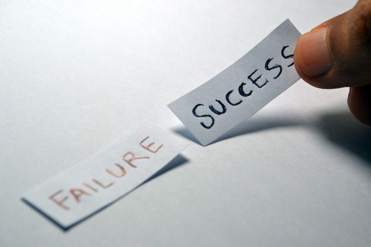 Persona seleccionando entre dos papeles uno de fracaso y otro de exito