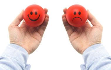 Persona con dos bolas en la mano una con una cara sonriente y otra triste