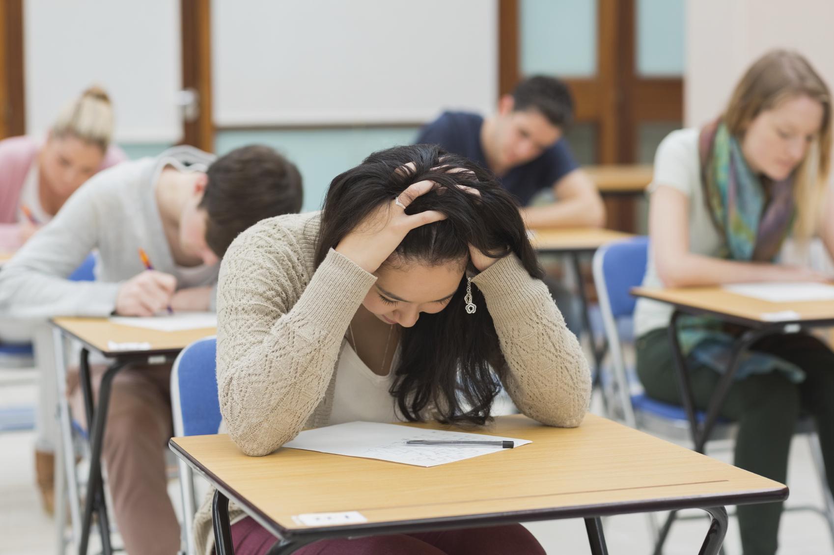 Persona sentada en una mesa con ansiedad mientras hace un examen