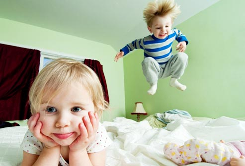 Dos niños desobedientes saltando sobre la cama