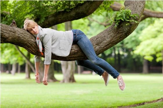 Persona cansada sobre un árbol por astenia primaveral