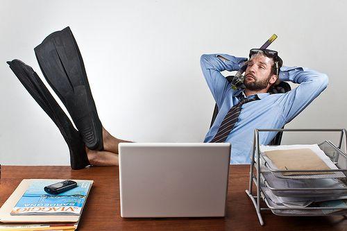 Hombre con los pies encima de la mesa por tener depresión postvacacional