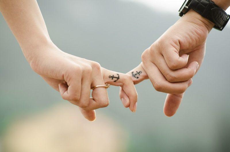 Dos personas que se dan la mano en una relación de pareja