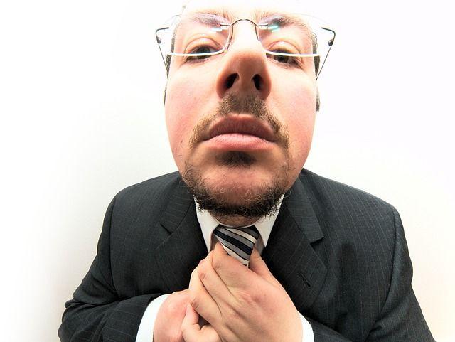 Persona con nervios y ansiedad que le aprieta el nudo de la corbata