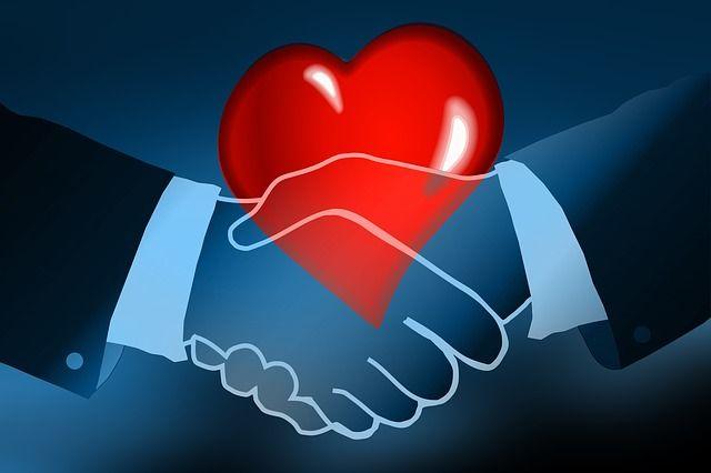 Dos manos estrechándose y un corazón representando los hábitos de vida saludable