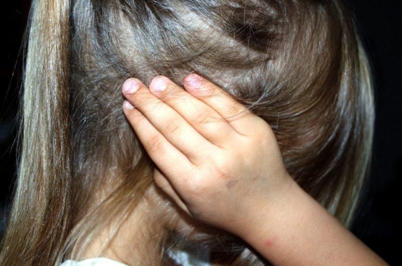 Niña desobedeciendo con las manos en los oídos por tener problemas de conducta