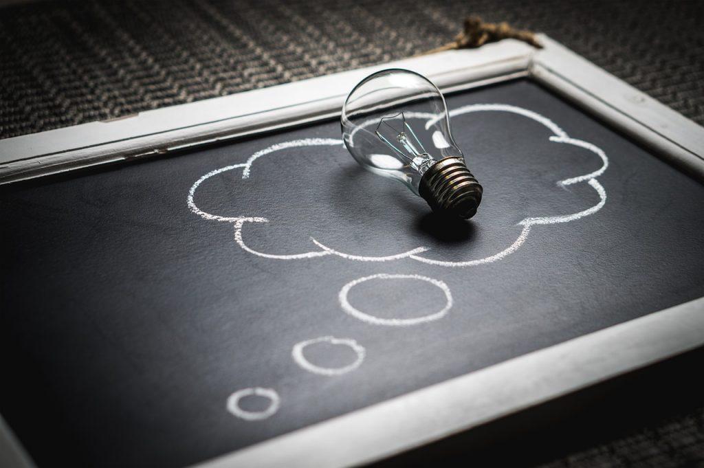 Pizarra con una bombilla y una nube de pensamiento representado la pregunta de cual es la diferencia entre psicólogo y psiquiatra