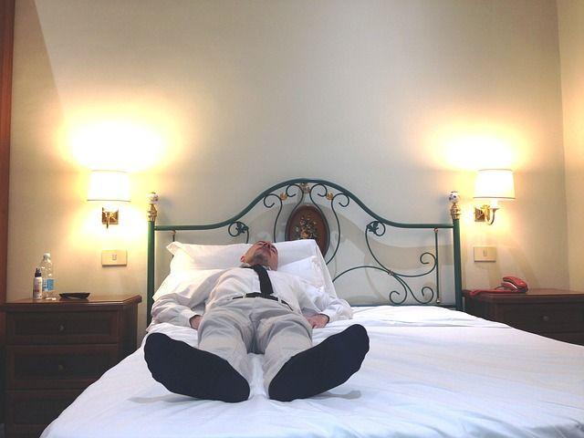 Persona agotada sobre la cama consecuencia del estrés laboral