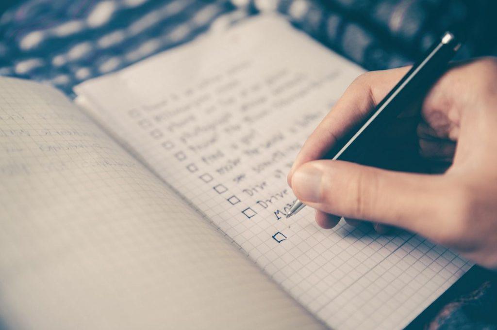Persona escribiendo sus planning semanal para administrar el tiempo