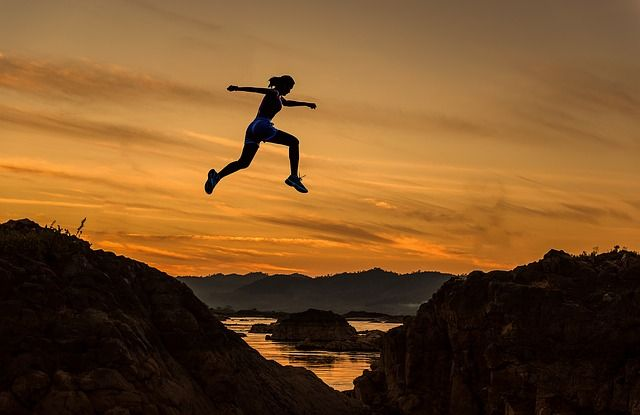 persona saltando entre dos montañas representando una definición de resiliencia
