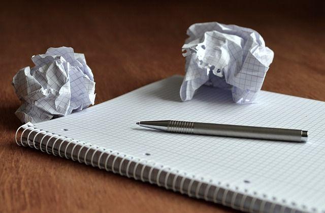 libreta con hoja en blanco, bolígrafo y papeles arrugados producto del perfeccionismo