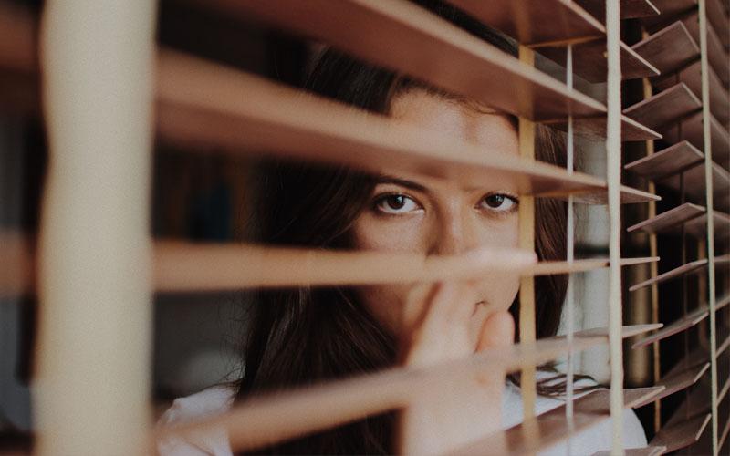 Mujer mirando por la ventana con síntomas de tener problemas de ansiedad