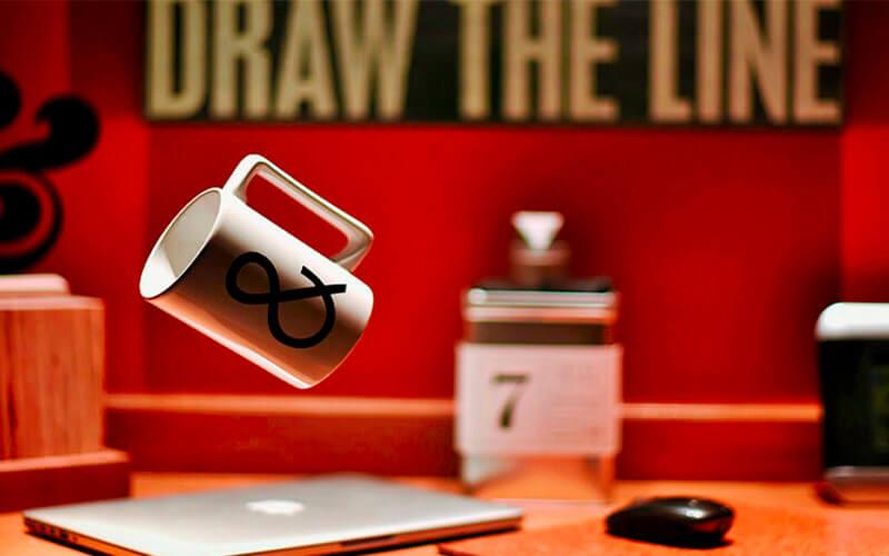 Taza flotando en una oficina alado de ordenador y ratón simulando el estres ocasionado por el síndrome de burnout