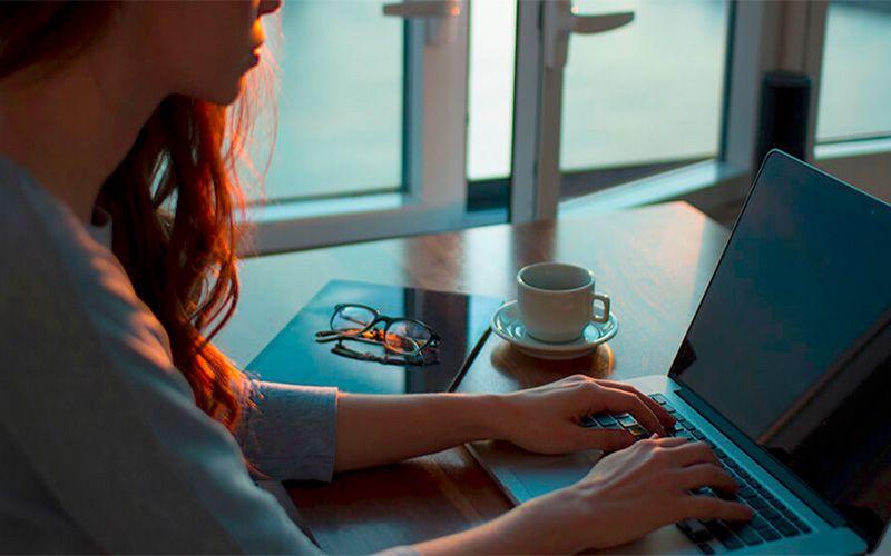 Mujer escribiendo en su ordenador padeciendo síntomas de síndrome de burnout