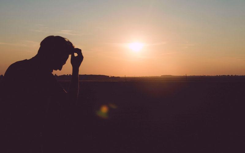 Persona sola al atardecer padeciendo un trastorno estrés postraumático