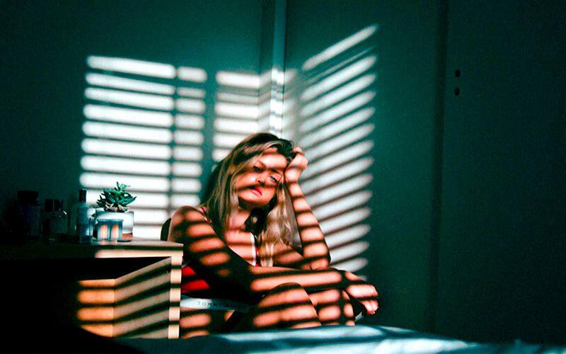 Personas agobiada sentada en una esquina de la habitación sufriendo un trastorno obsesivo compulsivo uno de los diferentes tipos de ansiedad