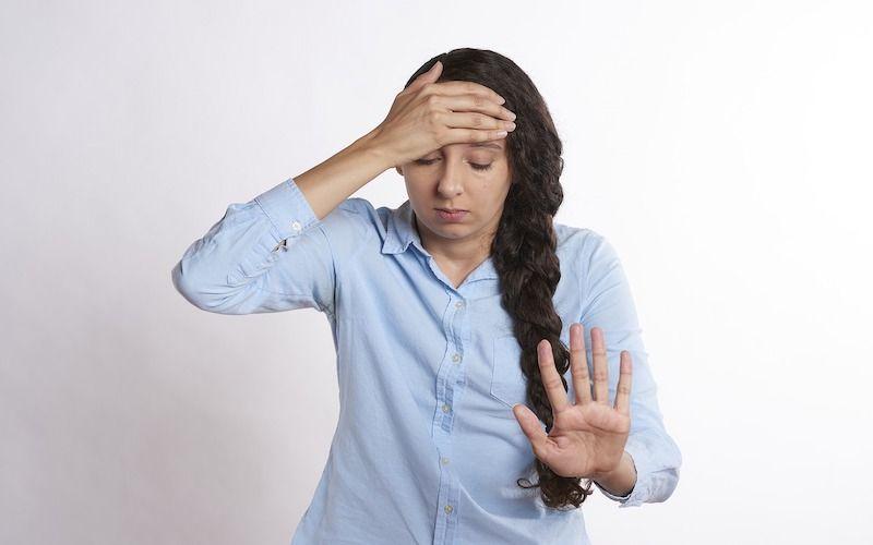 Persona en tratamiento por mareo por ansiedad con mano en la cabeza