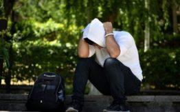 persona sufriendo mareo por ansiedad sentado en un banco