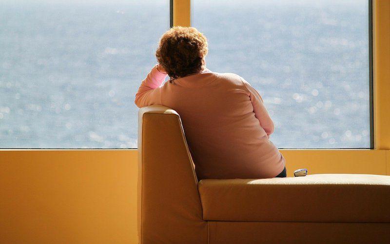 Persona con pensamientos intrusivos apoyada en la ventana