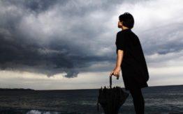 Mujer vestida de negro con el mar de fondo sintiendo angustia y ansiedad