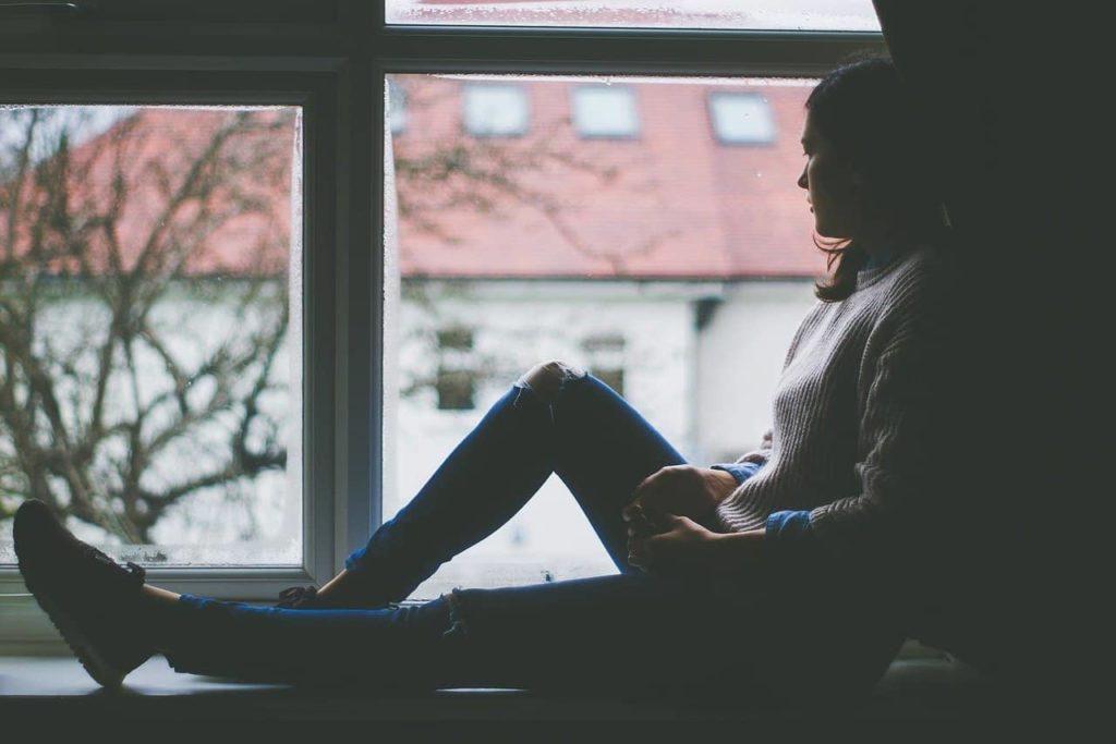 persona con ansiedad mirando por la ventana
