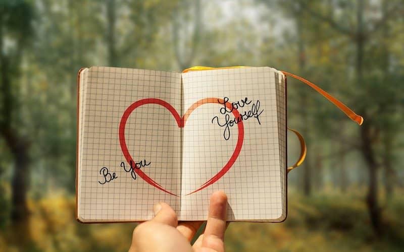 cuaderno con un corazón dibujado y palabras para mejorar la autoestima y salud